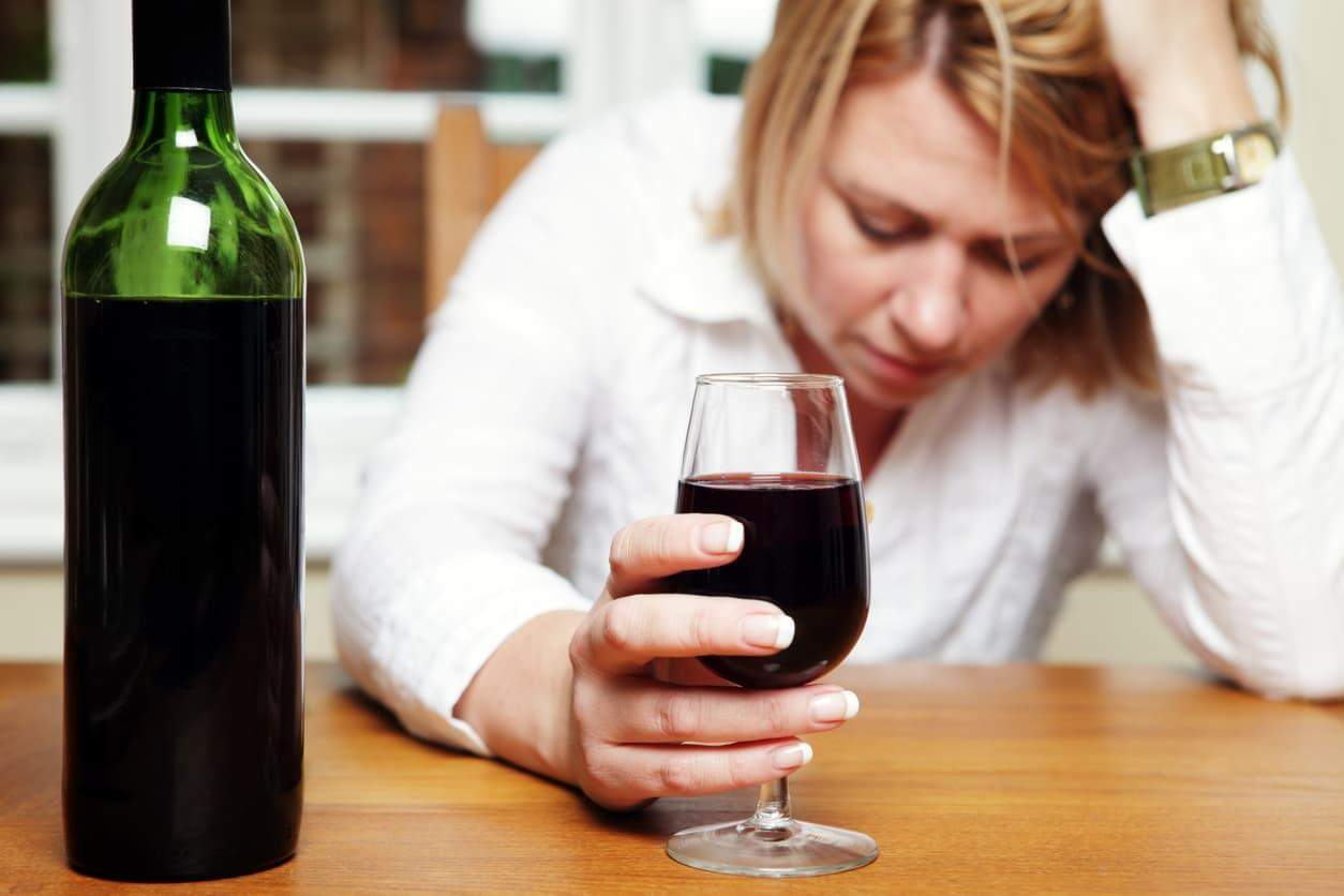 Depressed woman with alcohol addiction